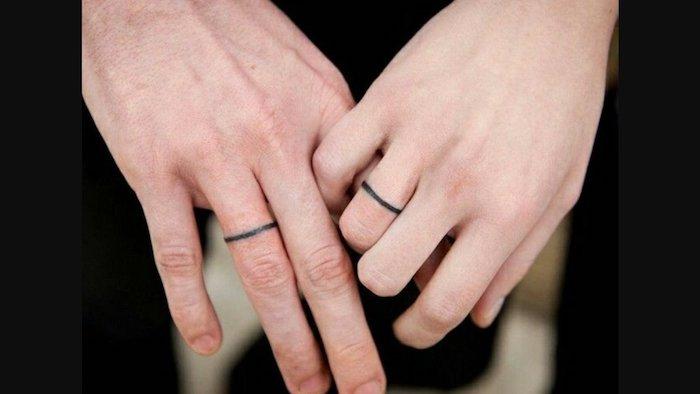liebes tattoo, zwei hnde mit kleinen schwarzen tätowierungen mit schwarzen ringen