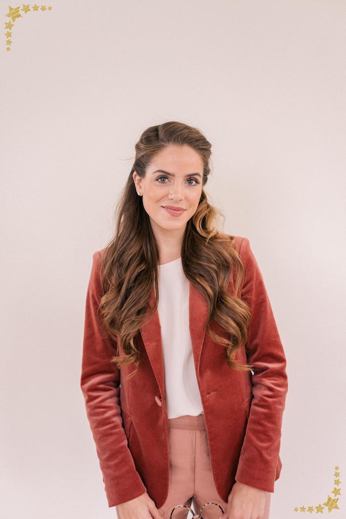 Halboffene lange Haare, natürliche Locken, roter Blazer und weißes Top, rosa Hose