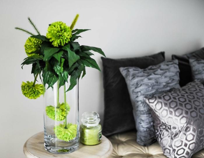 graue Kissen, grüne Pflanzen, ein kleiner runder Tisch, moderne Wandfarben