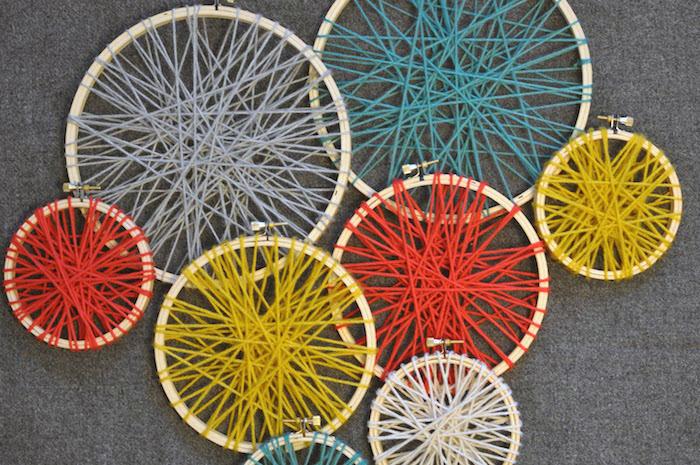 holzring basteln, viele strickrahmen in unterschiedlichen größen, grauer roter und gelber garn