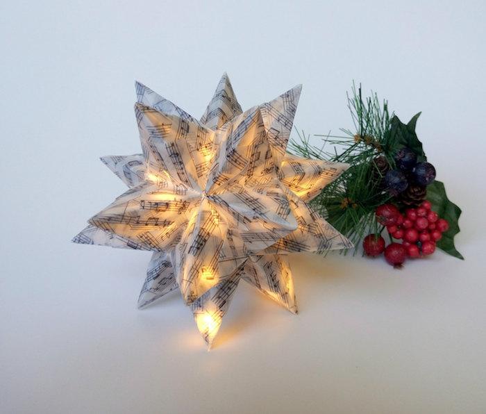ilex mit grünen blättern und vielen kleinen roten früchten, ein großer weißer bascetta stern mit vielen kleinen schwarzen noten, weihnachtsdeko selber machen