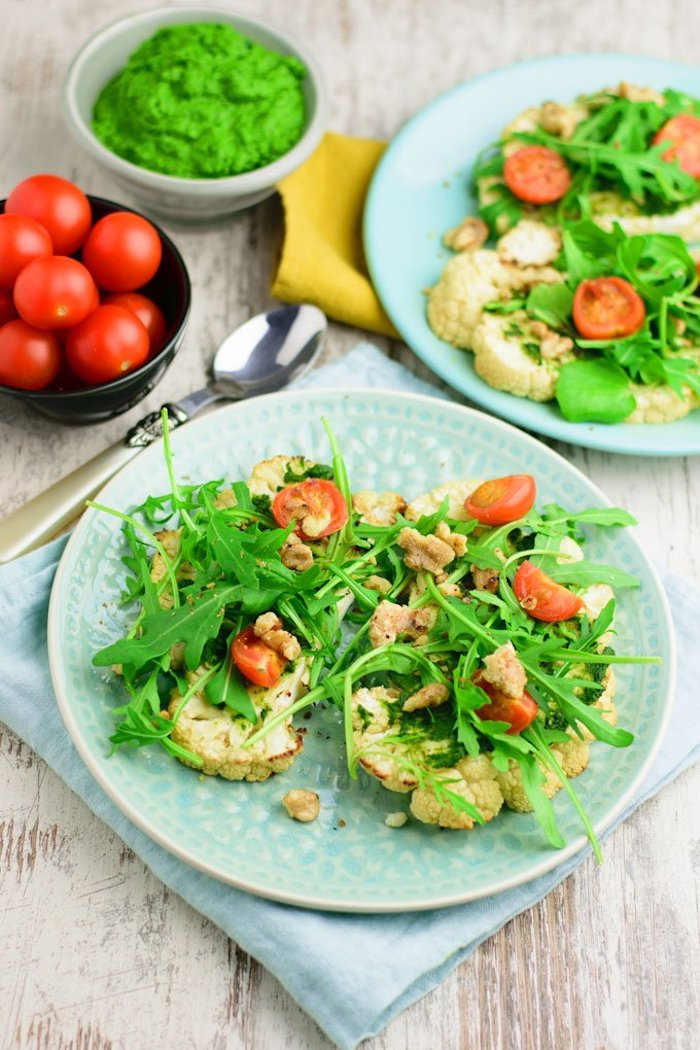 zwei blaue teller, cherry tomaten, kalorienarme lebensmittel, grüne salatblätter, karfiol
