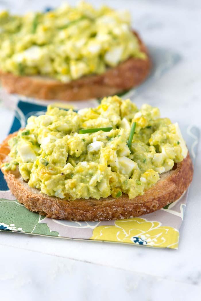 zwei brotscheiben, avocado mit einern, gesundes frühstück, kalorienarme lebensmittel