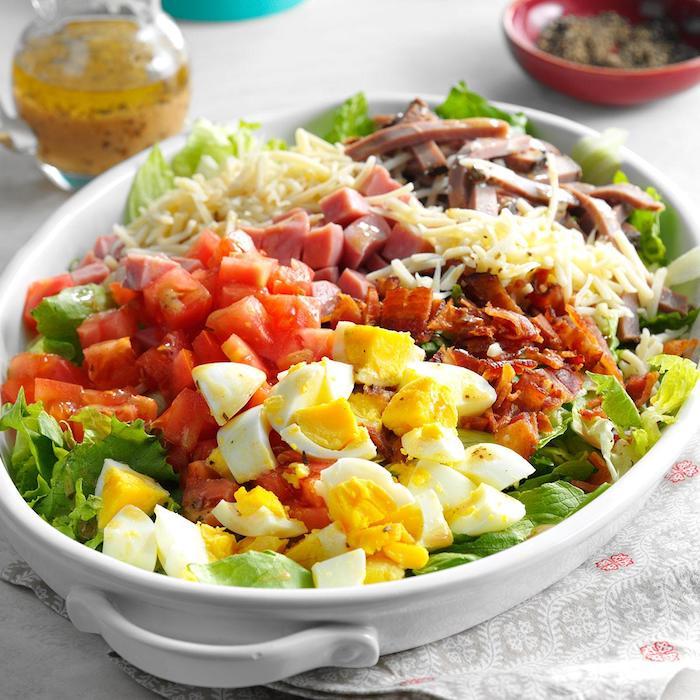 kalorienarmes essen, großer teller, salat mit einern, tomaten, schinken und käse