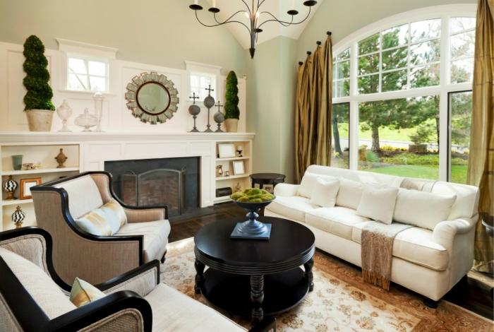 weiße Sofas und Sessel, runder Spiegel wie eine Blume, Wohnzimmergestaltung