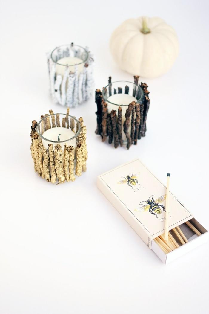 Kerzen selber verzieren, kleine Stäbchen kleben und mit weißem und goldenem Spray besprühen