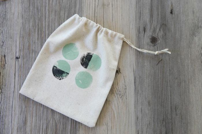 weiße Tüte mit grün und schwarz gestepelt, kleine Geschenktüten mit Faden zum Schließen