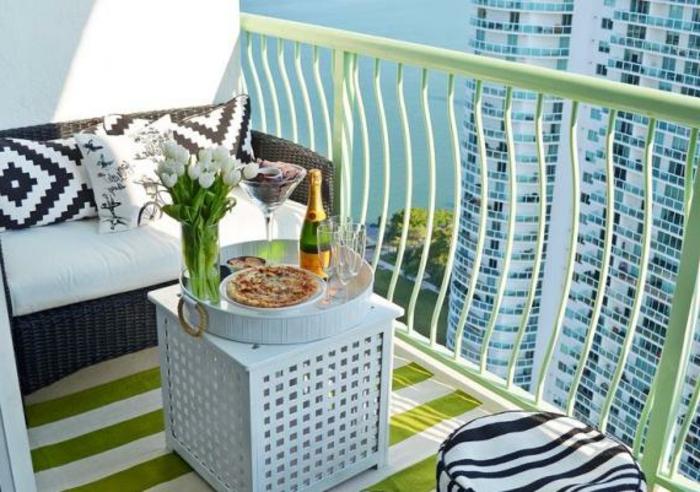 schlichte und stilvolle sitzecke balkon, quadratischer kaffeetisch in weiß mit einem tablett darauf, wein und pizza, weiße tulpen, deko ideen, kissen schwarz und weiß