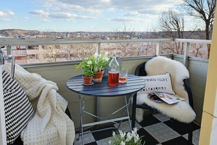 sitzecke balkon gemütlich mit den dekorationen: fellteppich, frische blumen, decke gegen kälte, kissen, kaffeerisch mit wein und schöne aussicht