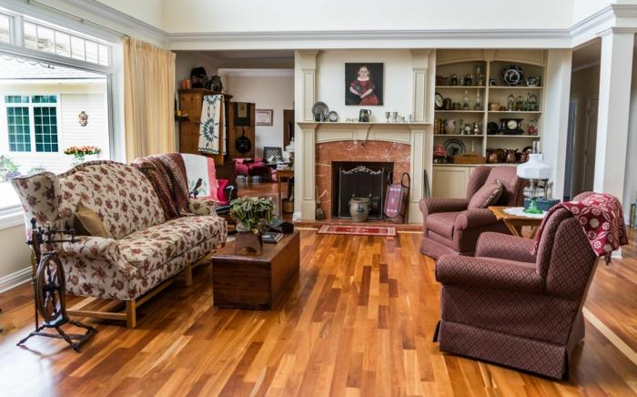 Wohnzimmergestaltung, zwei Sessel, buntes Sofa, Kamin und Regal, kleine Tische