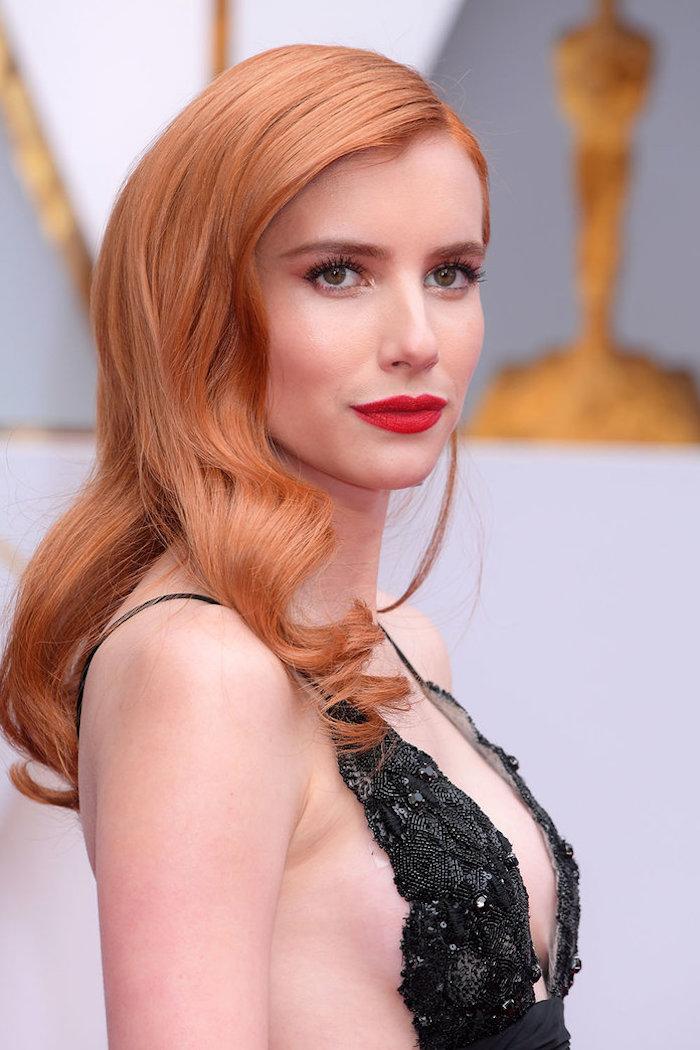 Lange offene Haare mit schönen Locken, roter Lippenstift und schwarze Mascara, schwarzes Abendkleid mit Kristallen