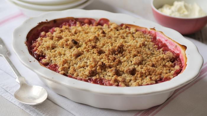 eine weiße schüssel mit einem roten erdbeer rhabarber kuchen mit einer roten erdbeer rhabarber marmelade, ein löffel und eine weiße decke, rezepte mit rhabarber pflanzen, rhabarber crumble