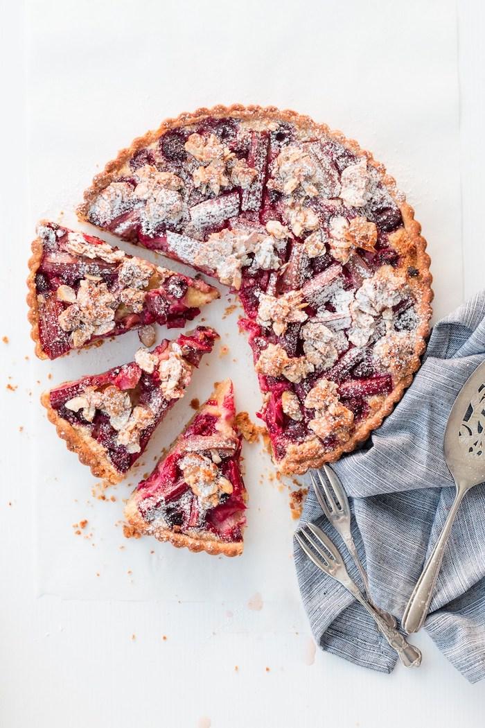 löffel und gabel und eine kleine blaue decke, ein großer roter erdbeer rhabarber blechkuchen, rhabarber rezepte