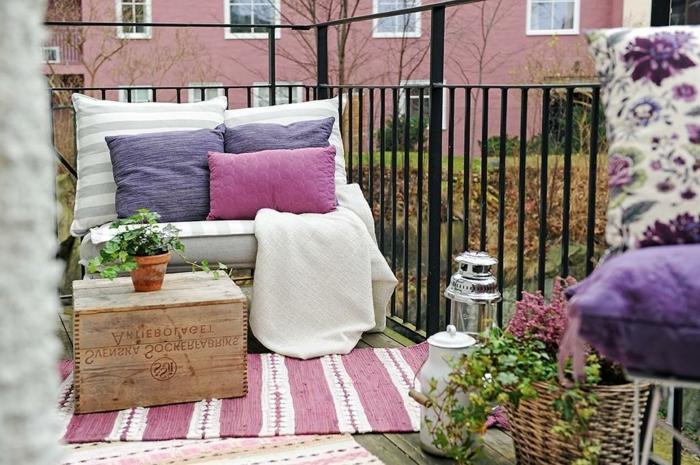 sitzecke balkon, rosarote kissen, lila dekorationen, teppich, hölzerner kasten als tisch nutzen, blumentopf