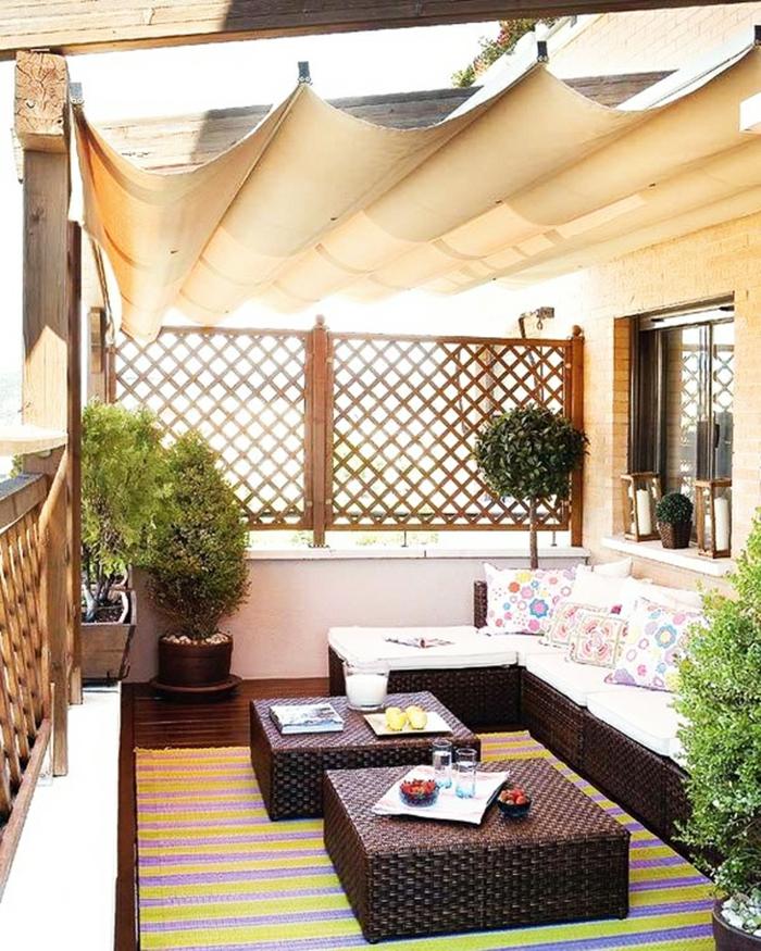 bedeckte sitzecke balkon, gemütlich mit einem rattan sofa und sessel, tisch, kleiner zaun, sichtschutz, sonnenschutz für entspannte momente zu jeder zeit