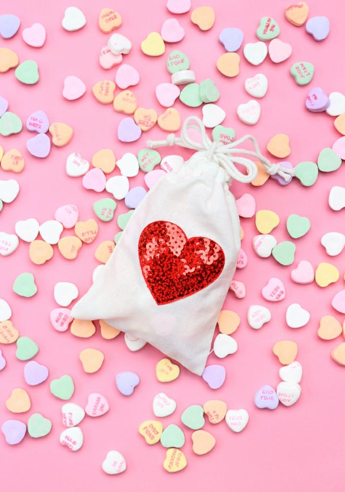 eine kleine weiße Tüte mit einem großen Herz aus Bügelperlen, kleine Geschenktüten voller Süßigkeiten