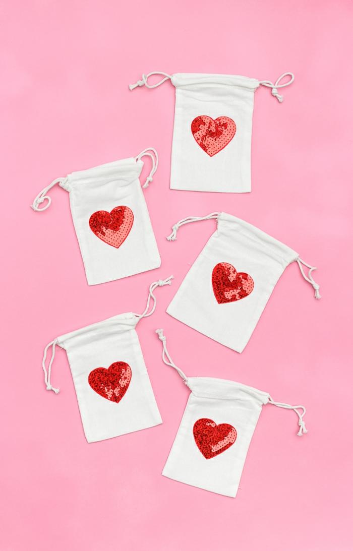fünf kleine Geschenktüte in weißer Farbe mit roten Herzen in der Mitte