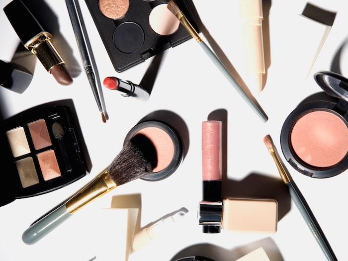 natürliches make up, schminkpinsel, rouge, roter lipoenstift, lidschatten in goldenen und braunen farben