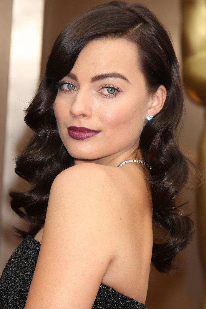 Lange Haare mit seitlichem Scheitel, Retro Locken, roter Lippenstift und schwarze Mascara, trägerloses schwarzes Kleid mit Pailletten, silberner Schmuck