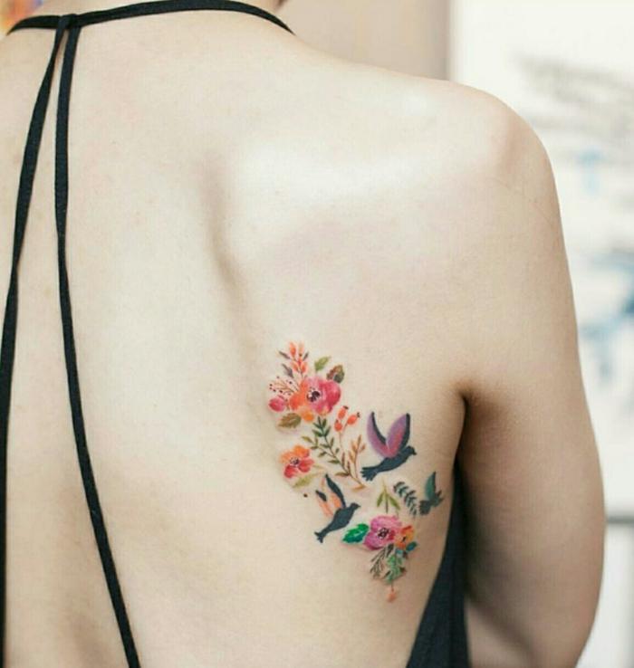 blumen und ihre bedeutung, viele kleine bunte blumen und drei kleine vögelchen als tattoo am frauenrücken