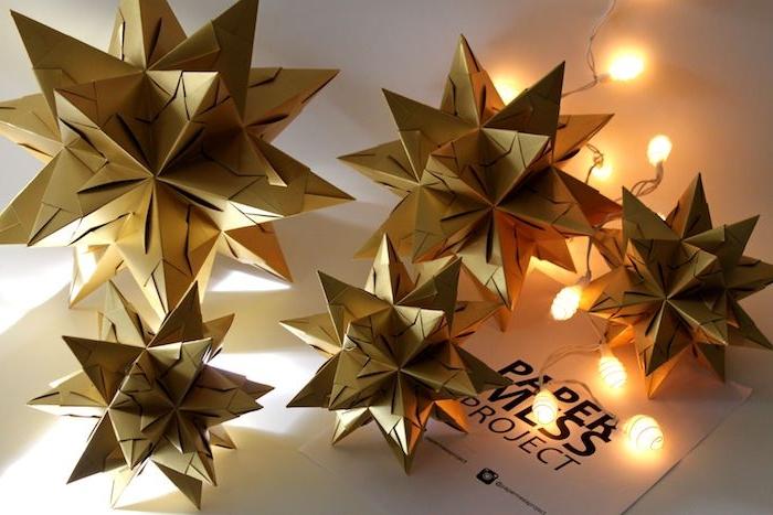 weihnachtsdeko selber basteln, fünf große gelbe weihnachtssterne aus papier und kleine gelbe leuchten, ein weißer tisch, bascetta stern beleuchtet