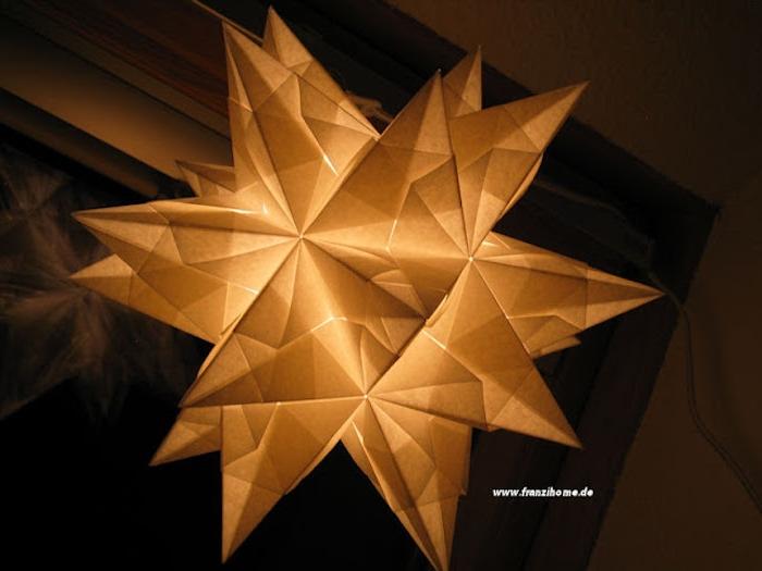 ein fenster und eine origami lampe mit einem großen weißen origami stern aus papier und mit weißen strahlen aus papier, bascetta stern basteln anleitung