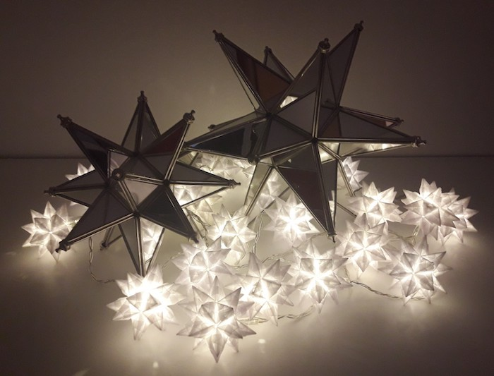 zwei große schwarze sterne aus einem schwarzen papier, viele kleine weiße leuchten mit kleinen weißen bascetta sternen aus papier, basteln mit papier