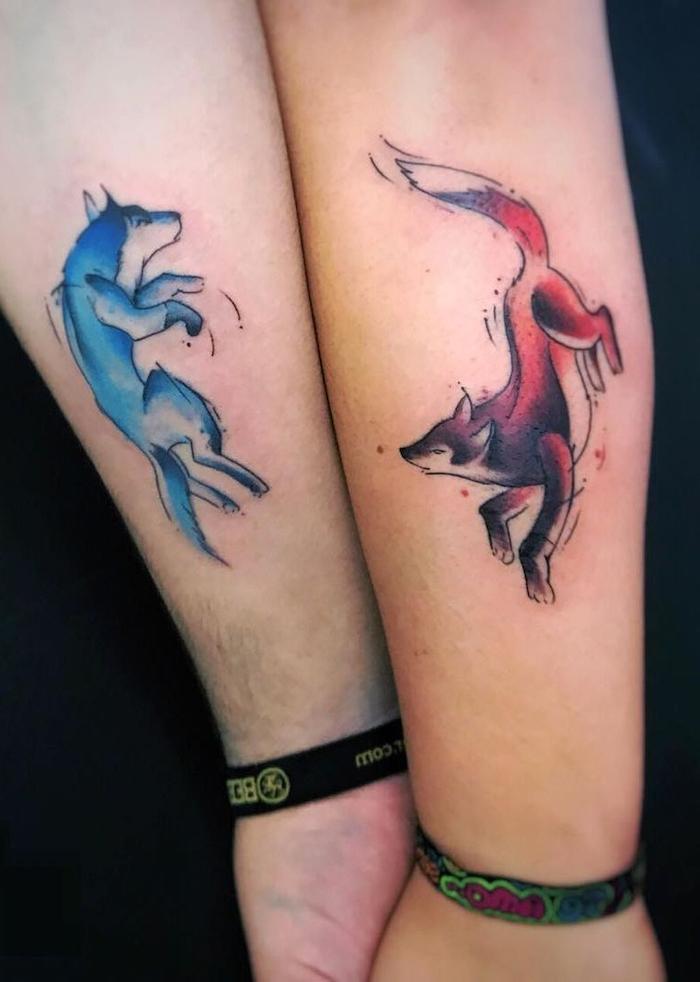 eine hand mit einem tattoo mit einem roten fuchs, tattoos für paare, ein mann mit einem partnertattoo mit einem blauen wolf