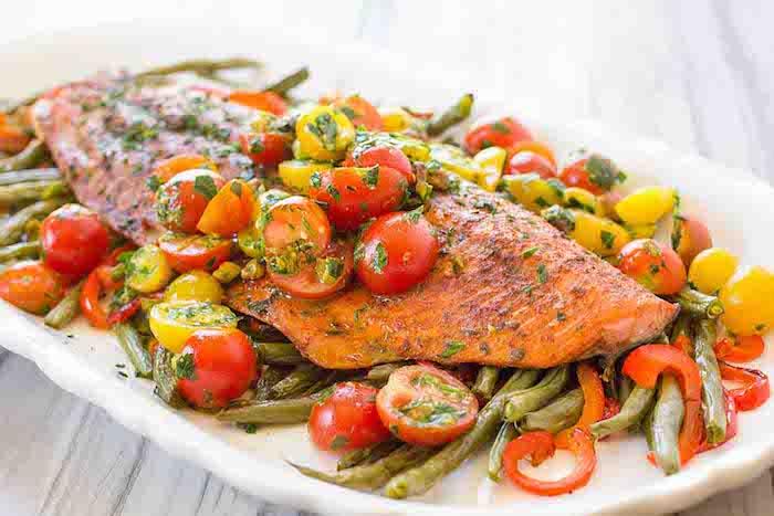 großer teller mit gebackenem fisch, salmon mit roten und gelben cherry tomaten, rezepte kalorienarm