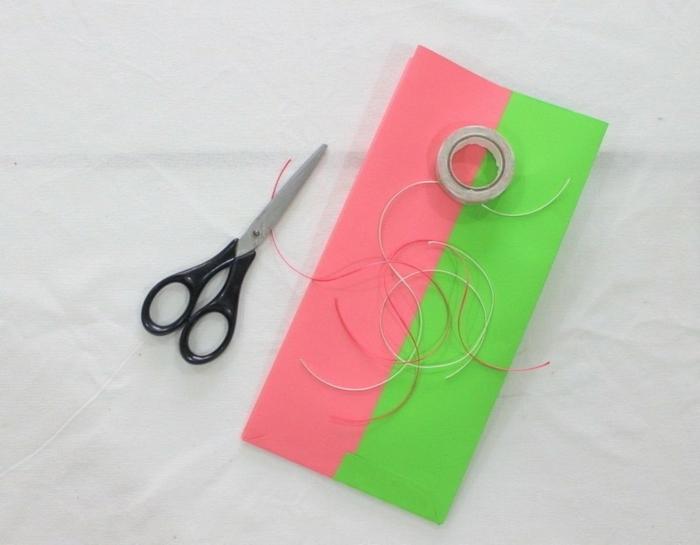 Klebstoff, eine Schere, kleine Papierstreifen, kleine Geschenktüten in Rosa und Grün