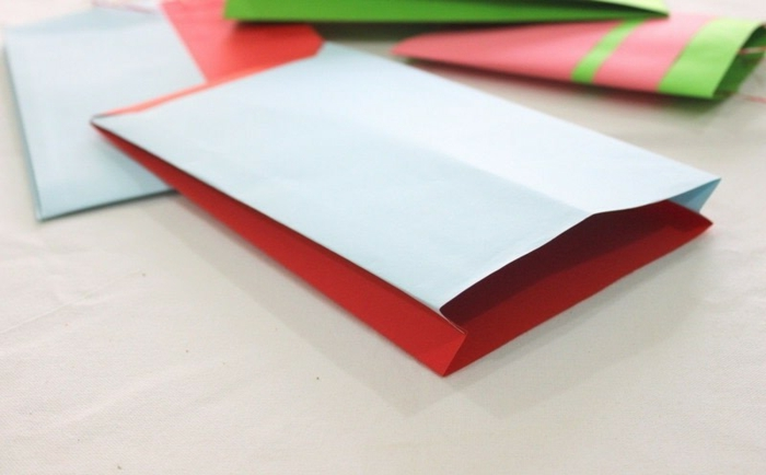 kleine Geschenktüten, in roter und blauer Farbe, wie sie zu falten sind