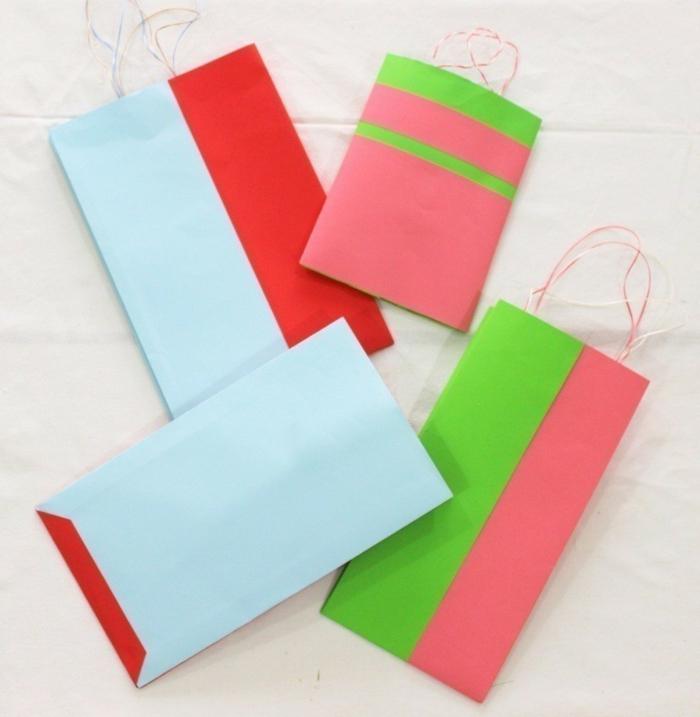 vier kleine Geschenktüten in Rot, Blau, Grün und Rosa mit kleinen Griffen