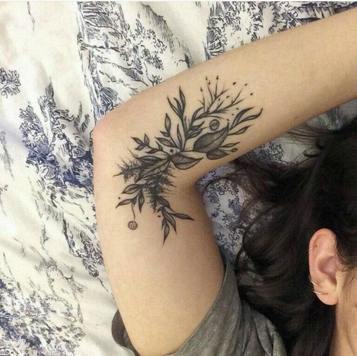 rosen tattoo schulter, eine frau liegt im bett und hat sich den arm gehoben, so dass das tattoo sichtbar ist, dezentes tatoo