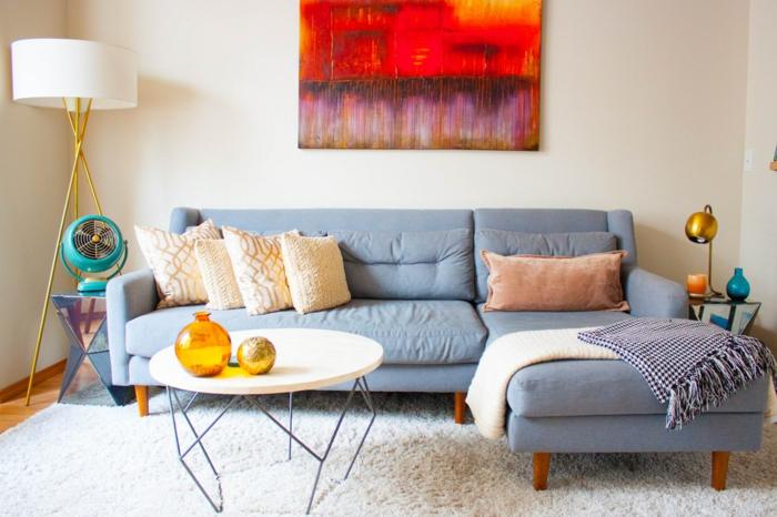 ein Ecksofa in blauer Farbe, kleine weiße Kissen, ein runder Tisch, weißer Teppich, Einrichtungsideen Wohnzimmer