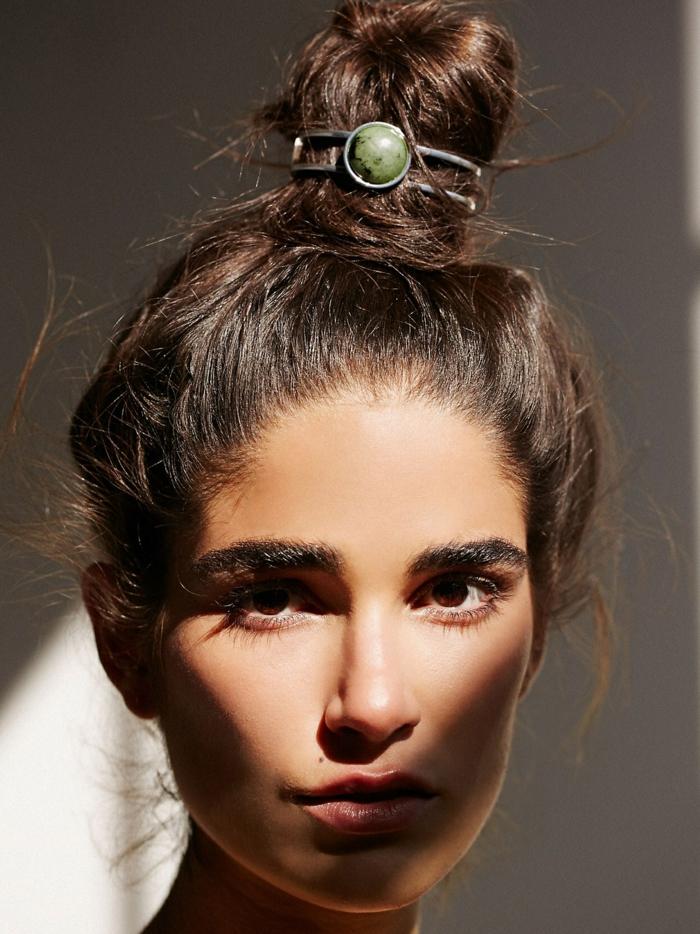 ein dunkelhaariges Mädchen, Dutt Haare wie eine Krone, grüner Stein am Kopf