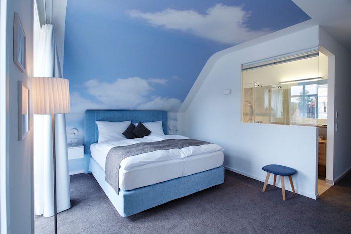 Schlafzimmer Einrichtung, blaues Boxspringbett, Wandfarbe Himmel und Wolken