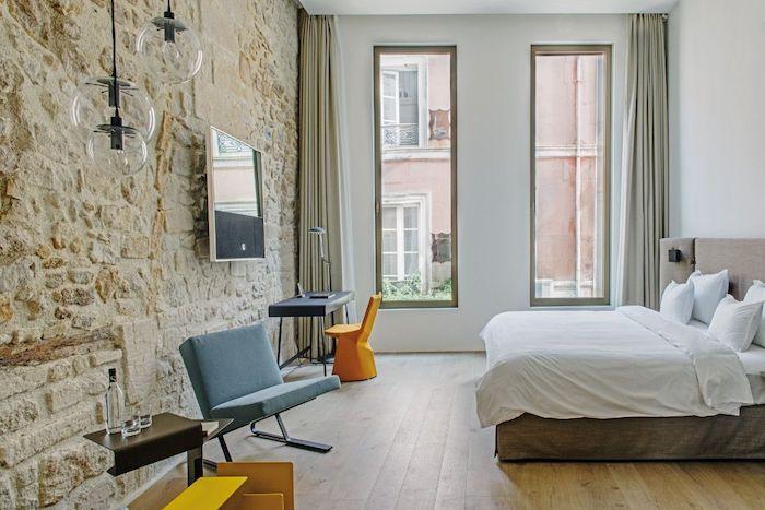 Schlafzimmer einrichten und gestalten, Steinwand und Holzparkett, weiße Bettwäsche