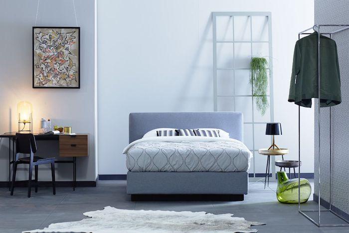 Schlafzimmer Einrichtung, Wandfarbe Weiß, blaues Boxspringbett, Schreibtisch aus Holz