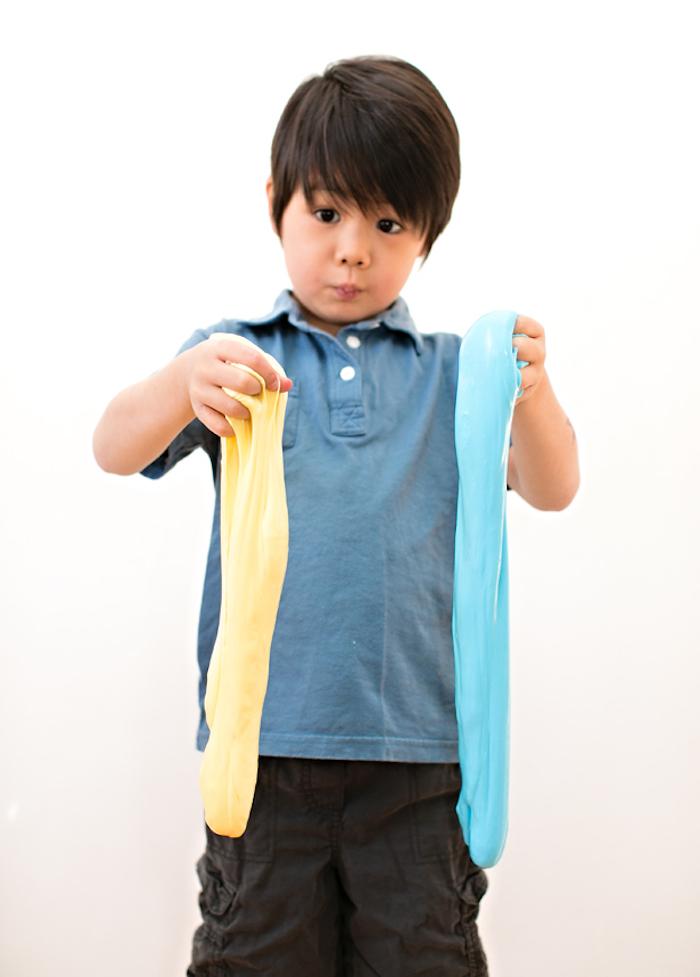 Gelber und blauer Schleim mischen, süßer Junge spielt mit Slime