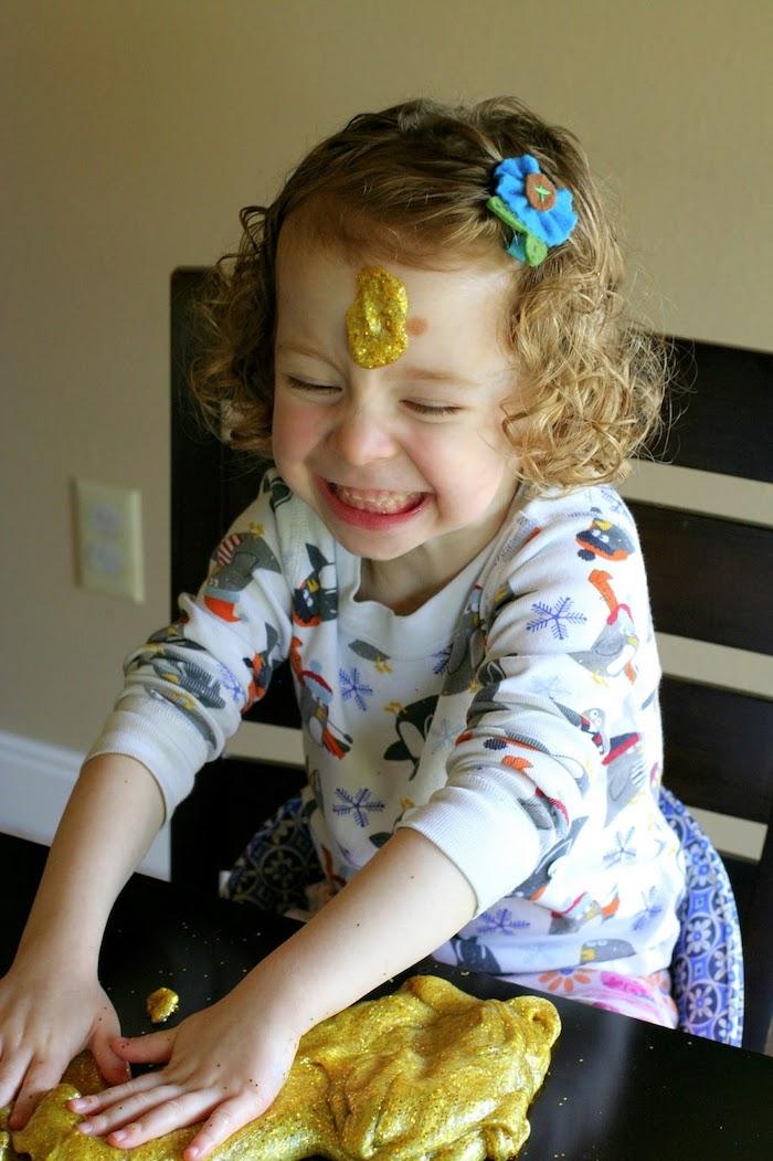 Kleines Mädchen spielt mit Schleim, Slime mit Glitter, Kind mit blonden Haaren, Bluse mit Pinguinen