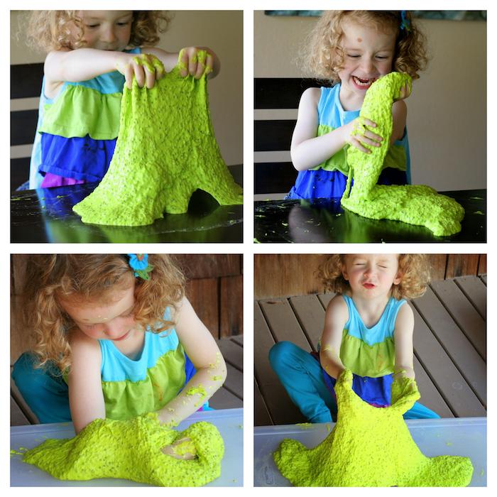 Süßes Mädchen spielt mit Schleim, Spaß haben, grüner Schleim, Kind mit blonden Haaren, mit Locken