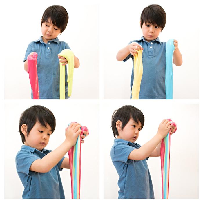 Kleines Kind spielt mit Schleim, Regenbogen Slime, Junge mit schwarzen glatten Haaren und Pony, blaues T-Shirt