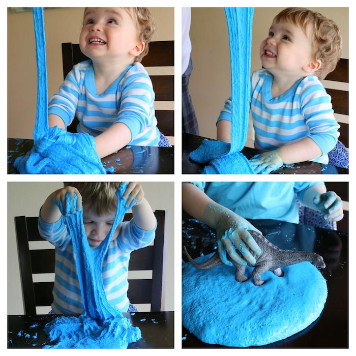 Mit Schleim spielen, blauer Schleim und Spielzeug Dinosaurier, süßes Kind mit blonden Haaren, gestreiftes T-Shirt