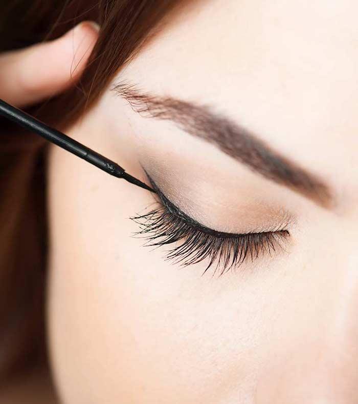 schminken für anfänger, frau, auge, schwarzer eyeliner ziehen, lange wimpern, augenbrauen