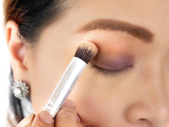 schminken für anfänger, lidschatten ausblenden, make up in orange und lila, schminkpinsel