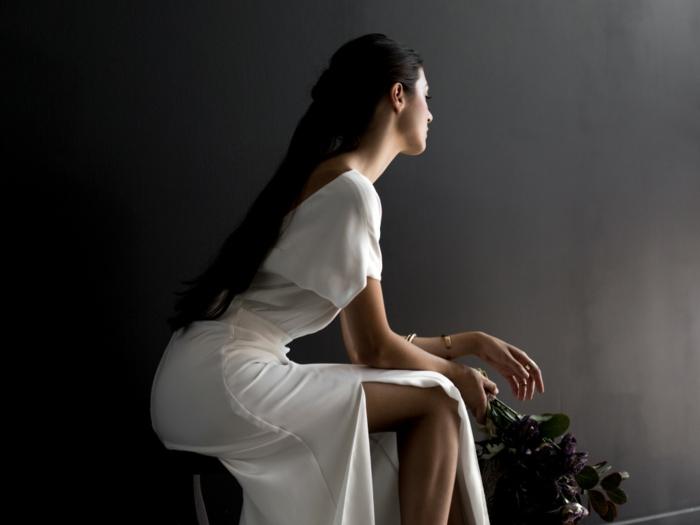 eine in Gedanken vertiefte Braut mit Rosenstrauß, Brautkleid vintage schlicht