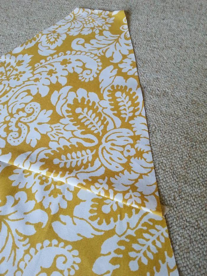 ein teppich und ein gelber stoff mit weißen blumen und weißeb blättern, bastelideen für erwachsene, ein tipi spielzelt selber bauen