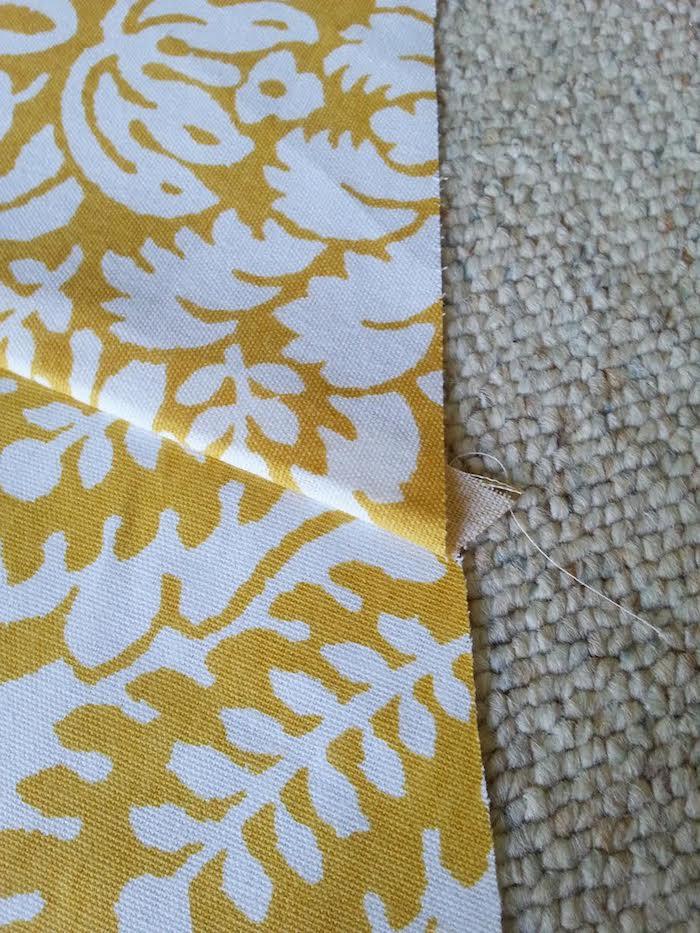 ein teppich und gelber stoff mit weißen blumen und weißen blättern, ein spielzelt tipi selber bauen, eine diy bauanleitung