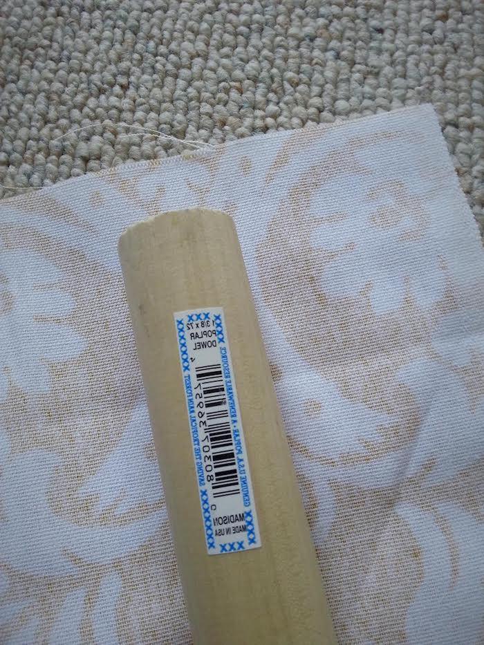 ein teppich und ein großer stock aus holz, ein gelber stoff mit vielen kloeinen und großen weißen blumen mit weißen blättern, eine diy bauanleitung
