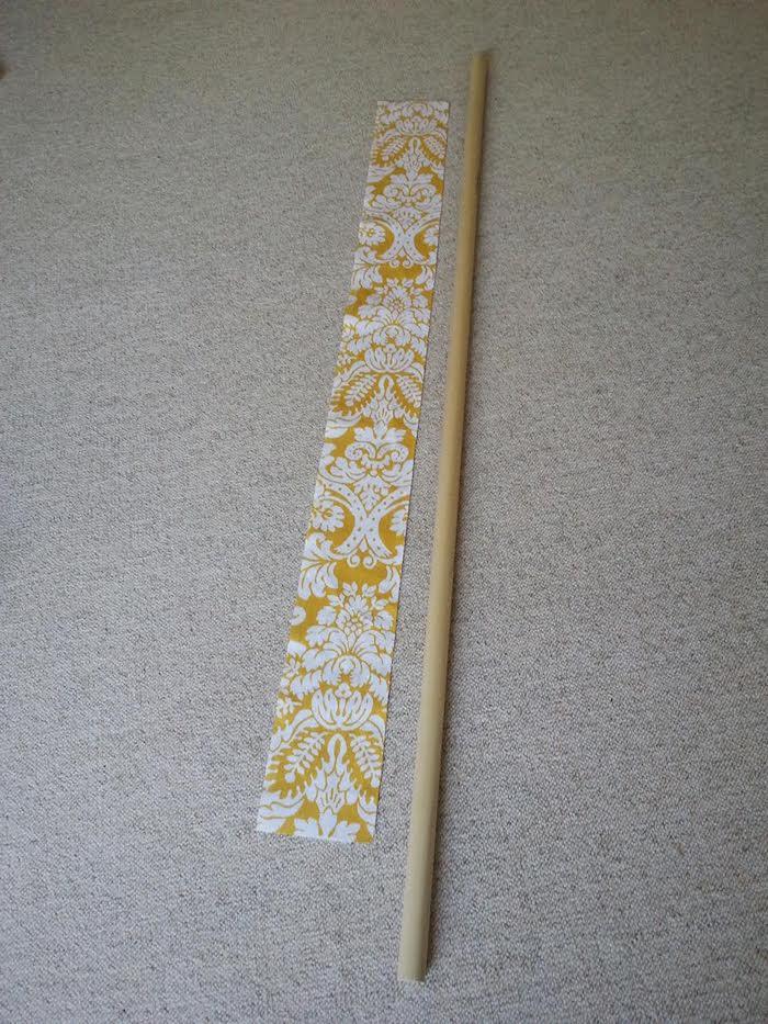 ein grauer teppich und ein langer stock aus holz, ein gelber stoff mit vielen kleinen und großen weißen blumen und weißen blättern, ein tipi kinderzelt selber bauen
